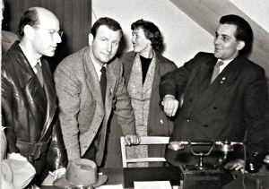Vier-Personen-Gruppe vor Schreibtisch in engem Zimmer.