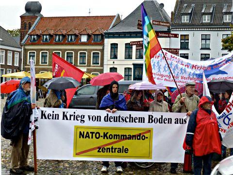 Demonstration mit Fahnen und Transparent: »Kein Krieg von deuschem Boden aus« und durchgestrichen: »NATO Kommandozentrale«.