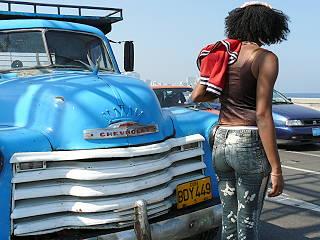 Kubanerin, blickt aus dem Bild; vorn angeschnitten blaues Auto.